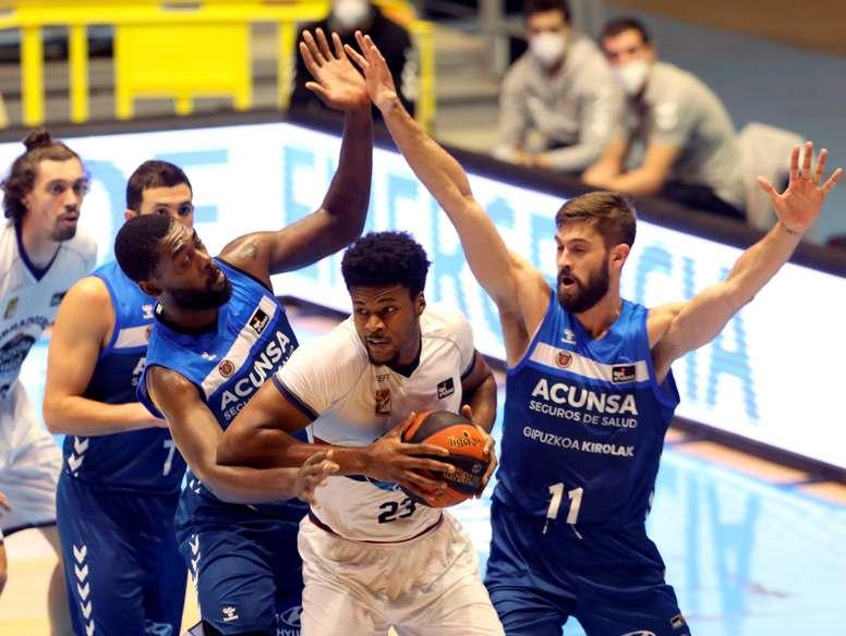 GRAEl jugador del Obradoiro Steven Enoch (c) protege un balón ante William Magarity (d) y Viny Okouo, ambos del Gipuzkoa Basket, durante el partido de la Liga ACB de baloncesto que disputaron en el Multiusos de Sar, en Santiago de Compostela. EFE/Xoán Rey
