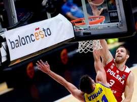 El jugador de la selección de Polonia Mihail Sokolowsky (d) trata de anotar ante la oposición del jugador de la selección de Rumanía Radu Virna, durante el partido clasificatorio para el Eurobasket de 2022 de este sábado en Valencia. EFE/Miguel Ángel Polo