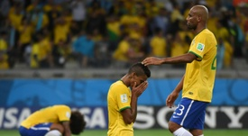 Brazil midfielder Luiz Gustavo (C) is consoled by teammate Maicon (R) at the Fifa world cup. AFP