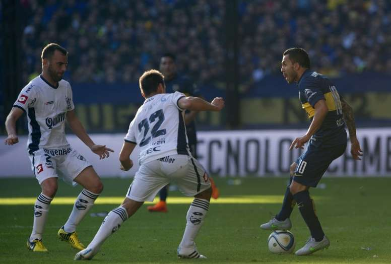 Carlos Tevez (R) vies for the ball with  Adrian Calello (C) and defender Mariano Uglessich during their Argentina First Division football match in Buenos Aires, Argentina, on July 18, 2015.