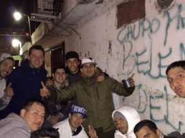 Carlos Tevez playing cards in the ghetto of Buenos Aires. Twitter