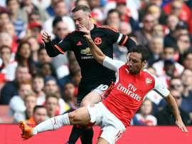 Cazorla y Rooney pelean por un balón en el encuentro entre el Arsenal y el United.