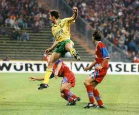Sutton shoots with two Bayern Munich players looking on back in 1993.