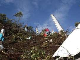 Des passants au milieu des décombres de l'avion accidenté.