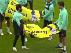 Elenco do Liverpool exibe bandeiras em alusão ao título inglês. DUGOUT