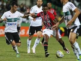 El jugador del Sao Paulo Thiago Mendes trata de zafarse de la presión de tres rivales del Coritiba en el encuentro que les enfrentó y que acabó con empate a un gol. SaoPauloFC