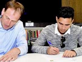 El nuevo futbolista del Vitesse Navarone Foor (d), en el momento de estampar su firma en el contrato que le vincula al club holandés. Vitesse