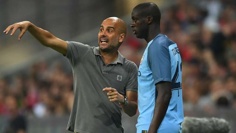 Guardiola (L) gives instructions to Toure. Goal