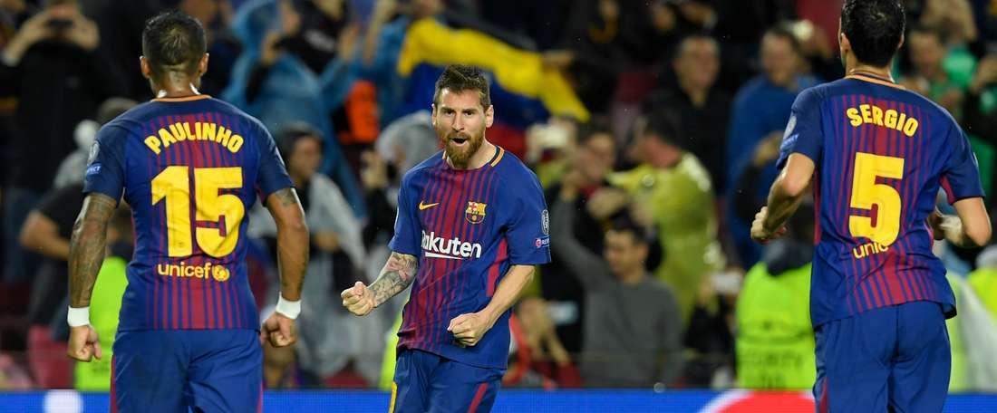 Lionel Messi, Paulinho et Sergio Busquets célébrant un but du Barça. GOAL