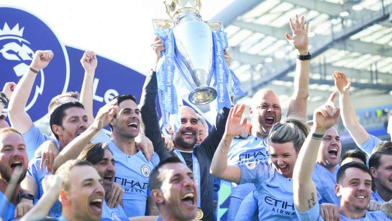 Pep Guardiola and his coaching staff with the Premier League trophy. GOAL