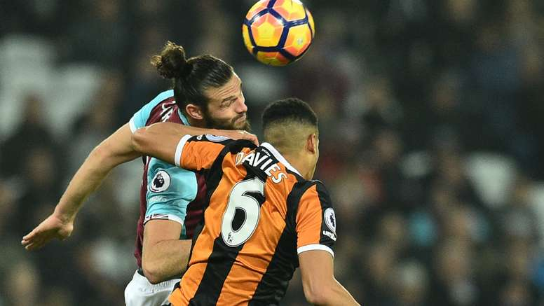 Andy Carroll challenges Hull defender Curtis Davies in the air. Goal