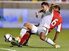 Henry Martín (de blanco, por México) y Radanfah Abu Bakr (de rojo, por Trinidad y Tobago) pelean por un balón dividido. Twitter