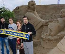 Hernán, Garrido y Dani Castellano, junto a Inés Jiménez, consejera de Turismo del Cabildo de Gran Canaria, posan para los medios ante el Belén de Arena de la Playa de las Canteras. UDLasPalmas