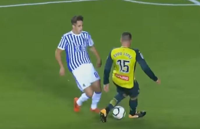 Januzaj le hace un caño a David López antes de dar el pase de gol a Illarramendi. Captura