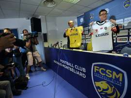Li Wing-Sang (C), CEO of Hong-Kong based company Ledus, and financial director Chi Hung Chiu (R) show the new jerseys of Sochaux football club on July 6, 2015 during a press conference at the Auguste Bonal stadium in Montbeliard