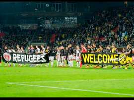 Los jugadores de St. Pauli y Borussia Dortmund sostienen unas pancartas de apoyo a los refugiados antes de iniciarse el encuentro. Twitter