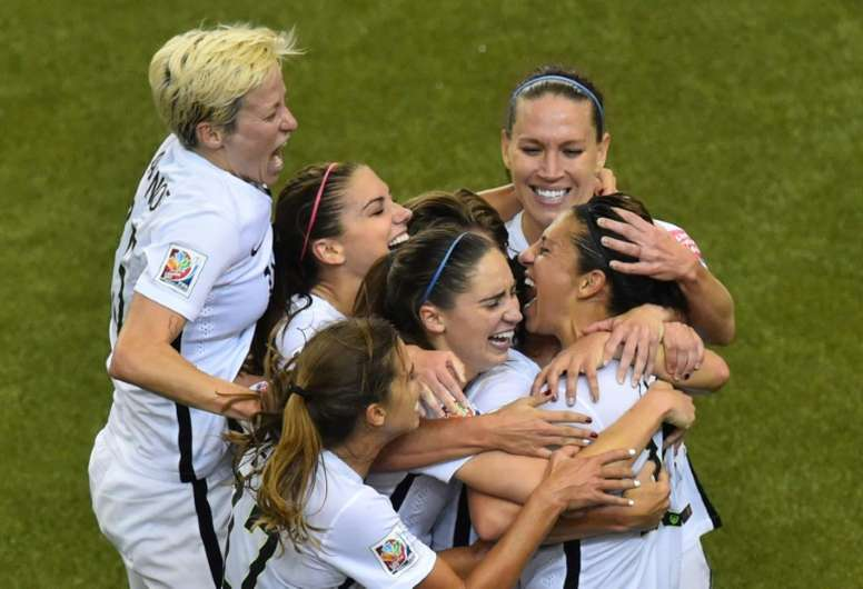 USA midfielder and goal scorer Carli Lloyd (R) celebrates with teammates during their 2015 FIFA Women World Cup semifinal match against Germany at Olympic Stadium in Montreal on June 30, 2015