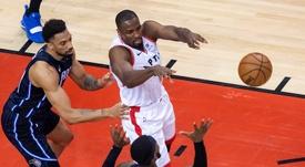 El jugador de los Raptors de Toronto Serge Ibaka (de blanco), lanza el balón a un compañero, ante la presión de Khem Birch (i) y Terrence Ross, de los Magic de Orlando, durante el partido de esta noche en Toronto. EFE