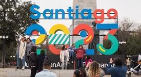 Un grupo de personas se toma fotografías este sábado frente a un cartel que anuncia la celebración de los juegos Panamericanos y Parapanamericanos 2023, en Santiago (Chile) durante el lanzamiento oficial de la capital como sede. EFE/Alberto Valdes