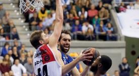 El escolta italiano Vitor Benite (c) del San Pablo Burgos entra a canasta ante el pívot estadounidense Ben Lammers (i) del Retabet Bilbao Basket, durante el partido de la decimotercera jornada de Liga Endesa que se disputó en el Coliseum de Burgos. EFE/Santi Otero